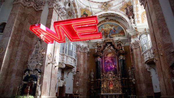 Das ist moderne Kunst: Eine Leuchtreklame im Dom und eine Jesusstatue als Uhr in der Spitalskirche